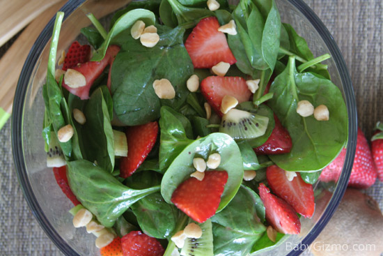 spinach strawberries and nuts in a bowl