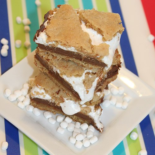 three smores cookie bars on white plate with marshmellows