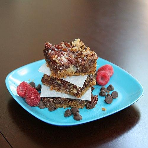 three raspberry dessert bars stacked on plate