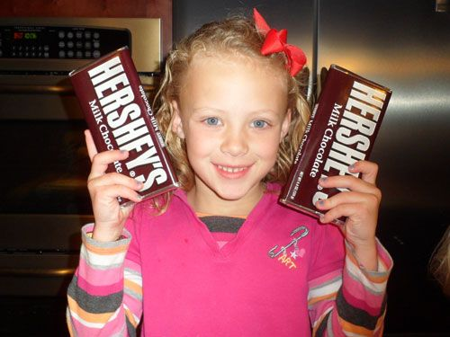 little girl with two candy bars