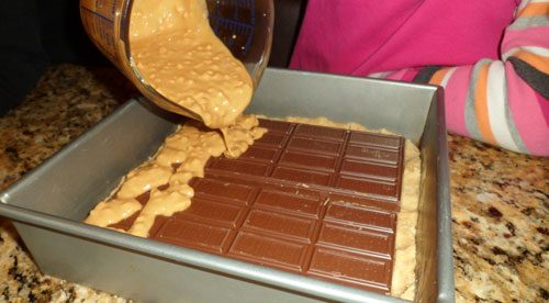 peanut butter being poured over chocolate bar in baking pan