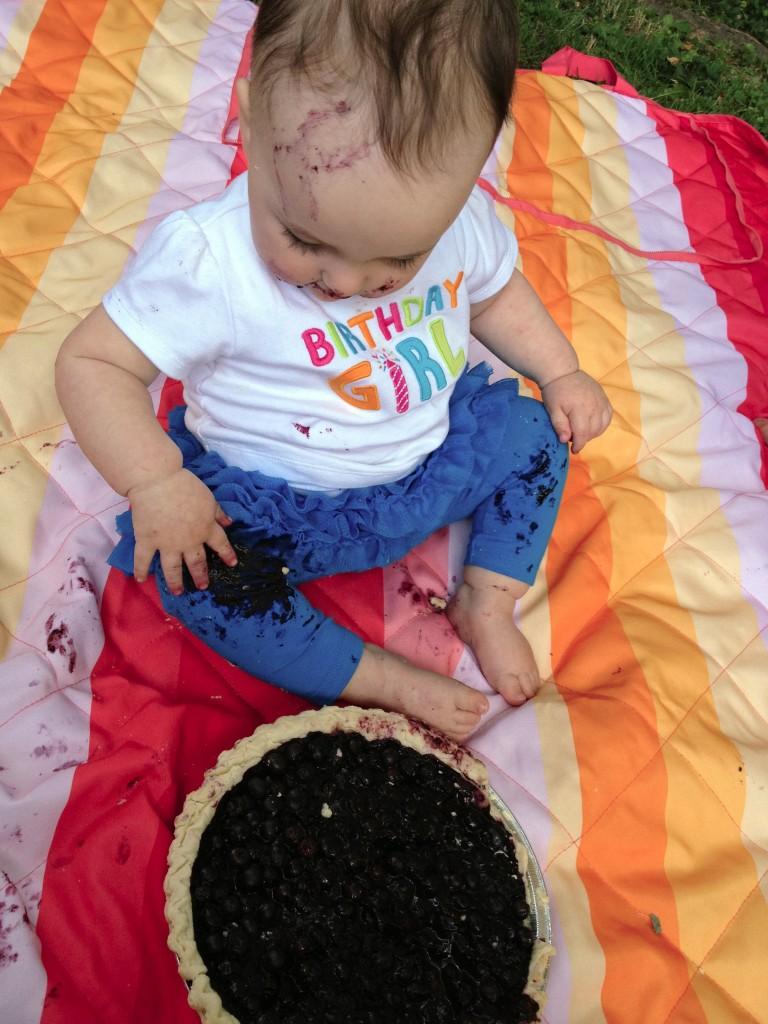Messy birthday girl on rainbow blanket next to pie