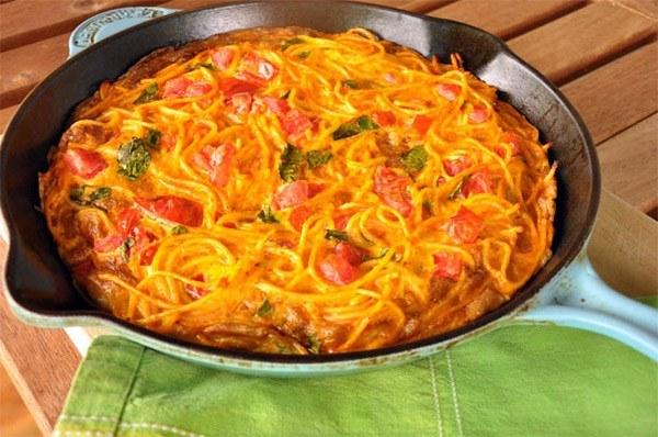 Spaghetti Frittata in a skillet on green cloth