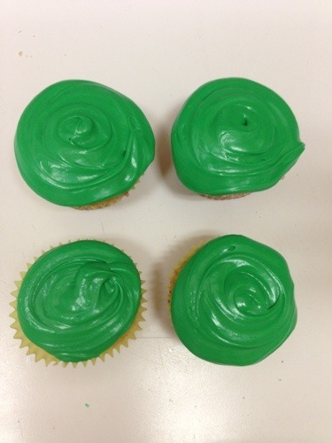 four vanilla cupcakes with green icing