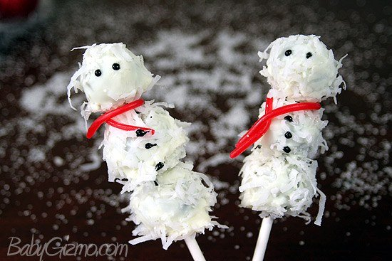 two Oreo Truffle Snowman on sticks with snow in background