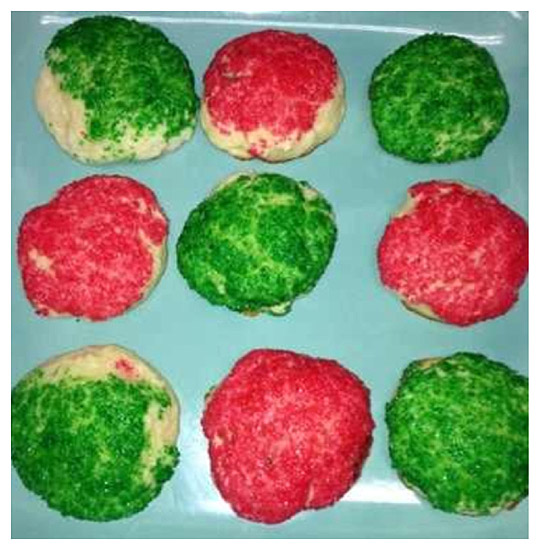 red and green sprinkles on cookie dough on blue plate