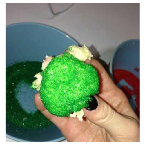 cookie dough dipped in green sprinkles in hand