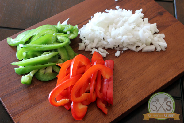 green peppers red peppers and chopped onions on cutting board