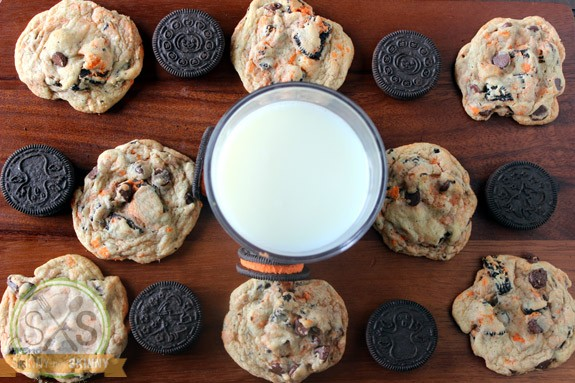 cookies on cutting board around glass of milk